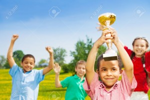 20981376-Close-shoot-of-black-happy-smiling-little-boy-holding-prize-cup-with-group-of-boys-and-girls-on-back-Stock-Photo
